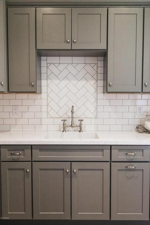 kitchen-sink-backsplash-tiles-white-herringbone-tiles-gray-cabinets.jpg
